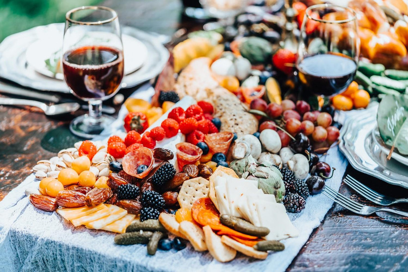 charcuterie board on table with glasses of red wine