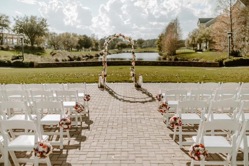 romantic outdoor wedding aisle decor idea floral pomanders hanging on the sides of chairs down the aisle