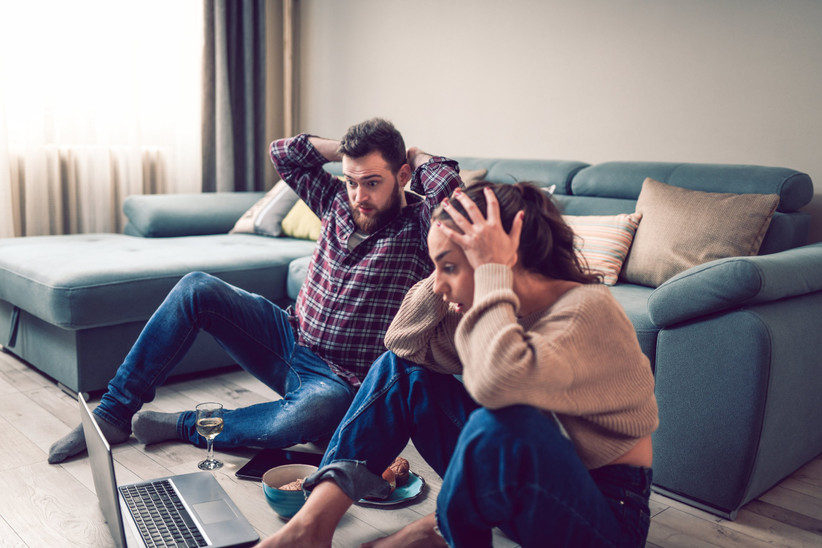 stressed out couple sitting on floor in front of computer