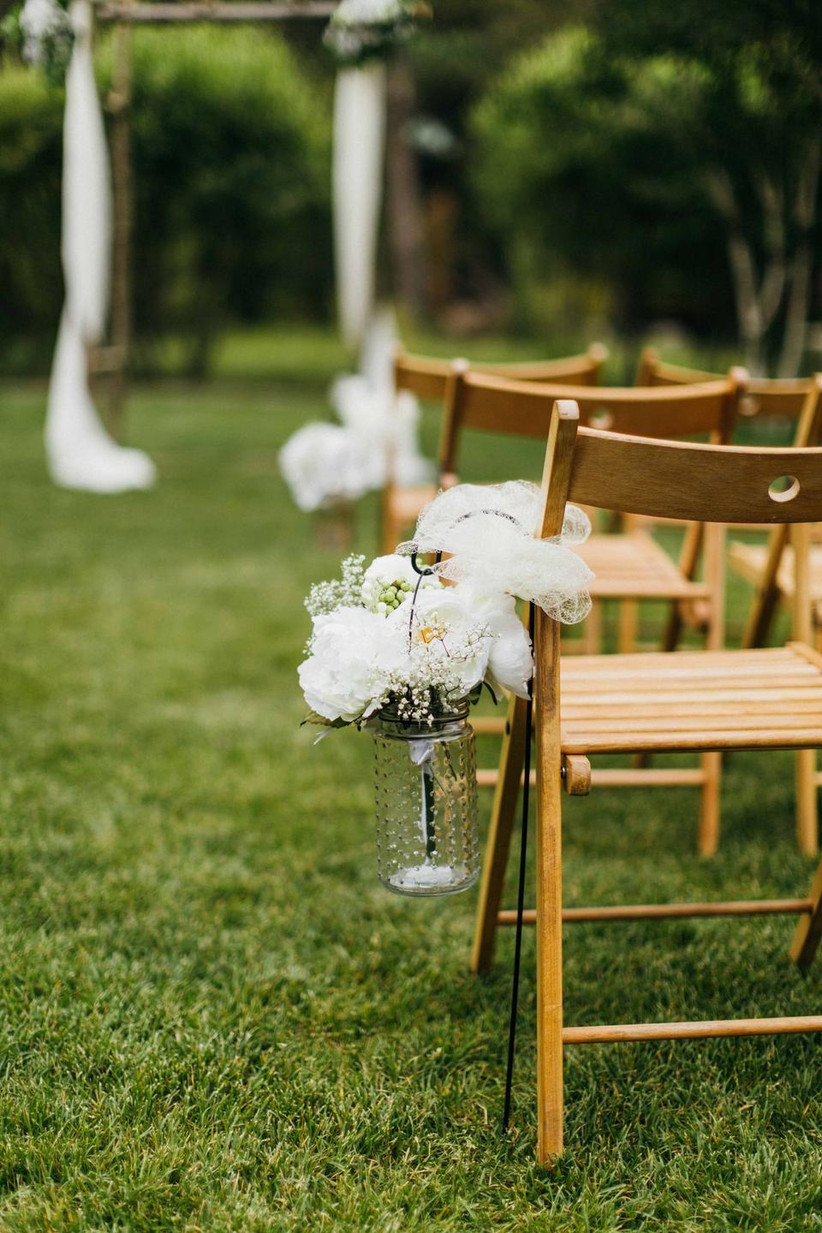 simple outdoor wedding aisle decor idea glass hobnail jar with white flowers and baby's breath displayed on small shepherd's hook