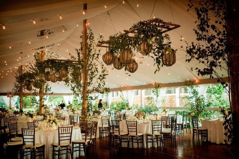 wedding reception tent with rattan lantern chandeliers decorated with greenery