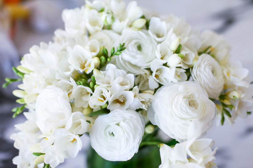 wedding centerpiece with white freesias and ranunculus