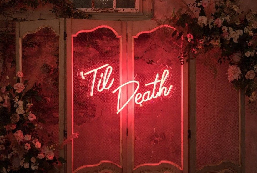 neon sign with 'til death written in pink letters