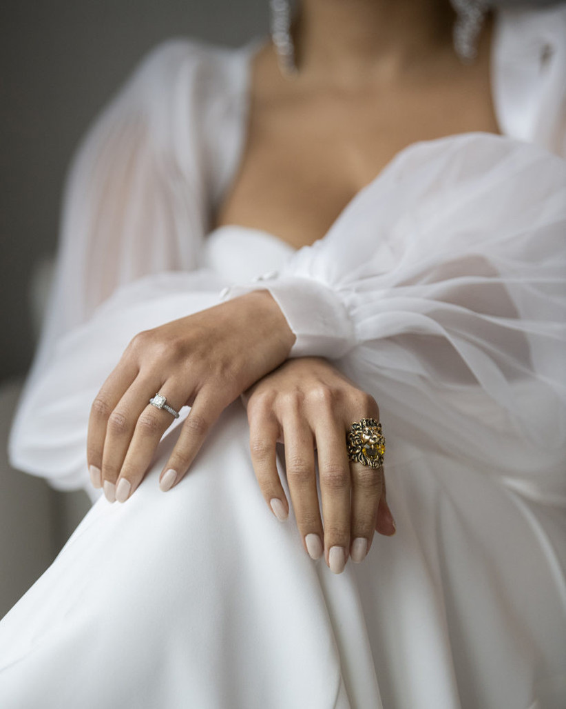 close-up of Black bride's hands crossed on her lap showing off classic solitaire round engagement ring