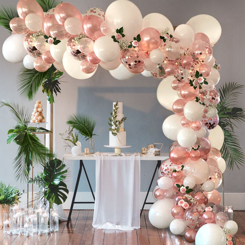 Extravagant rose gold and white balloon arch over cake table with tropical greenery