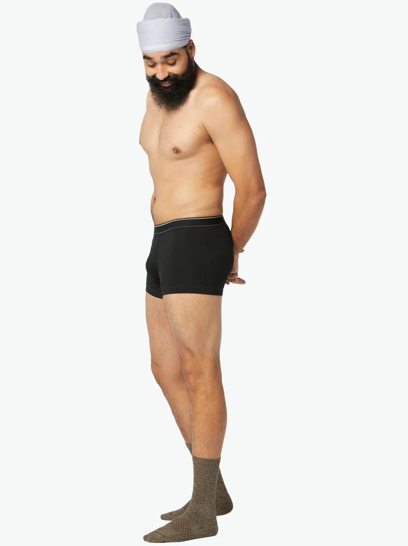 Model wearing snug black trunks and brown-green socks