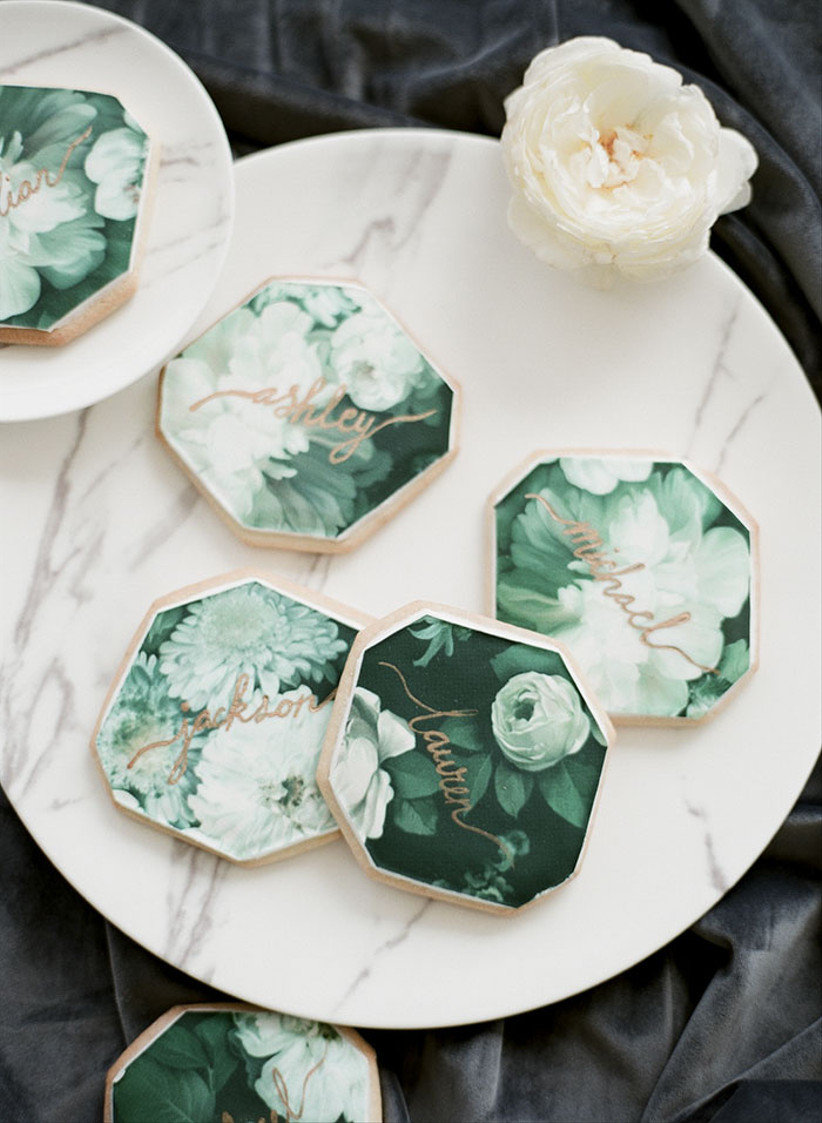 sugar cookies decorated with printed monochromatic green floral motif and guest names written in gold edible ink