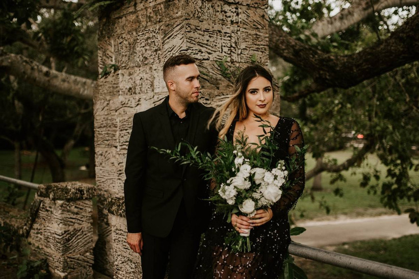 bride and groom wearing all black stand outside