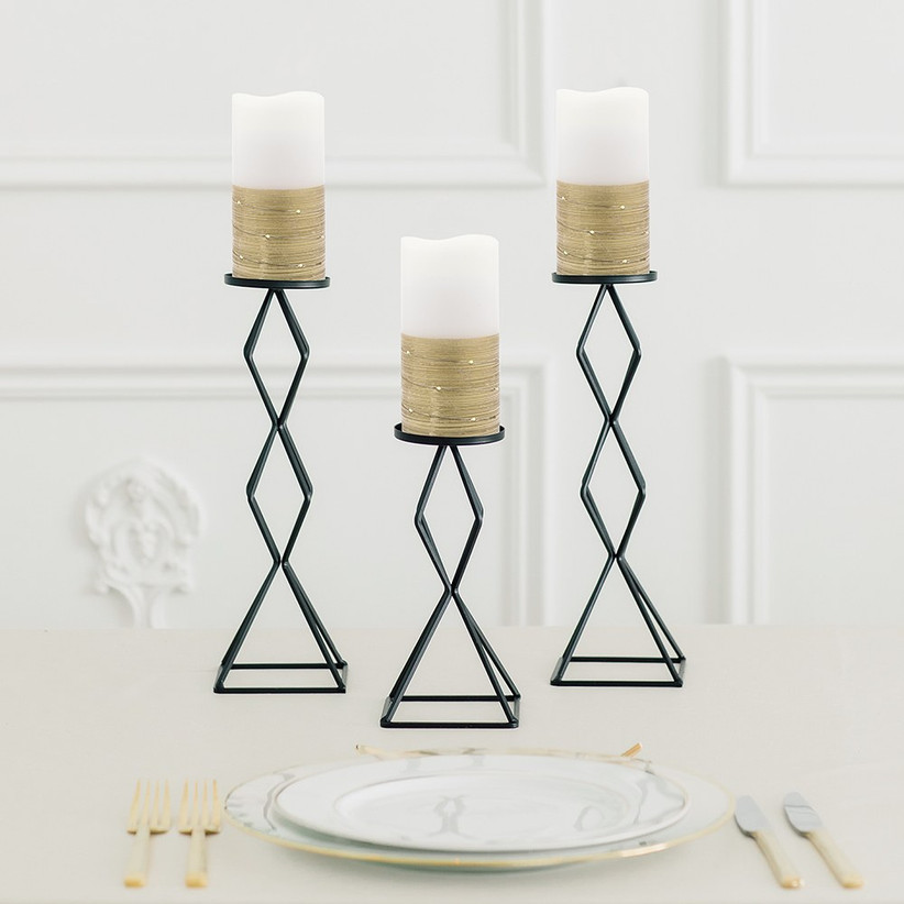 White and gold candles on tall black stands engagement party decoration idea