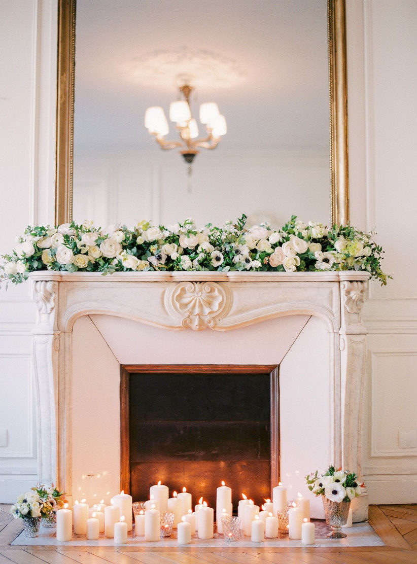 ornate white mantle topped with a gold mirror and fresh flowers with candles on the ground in front of the fireplace