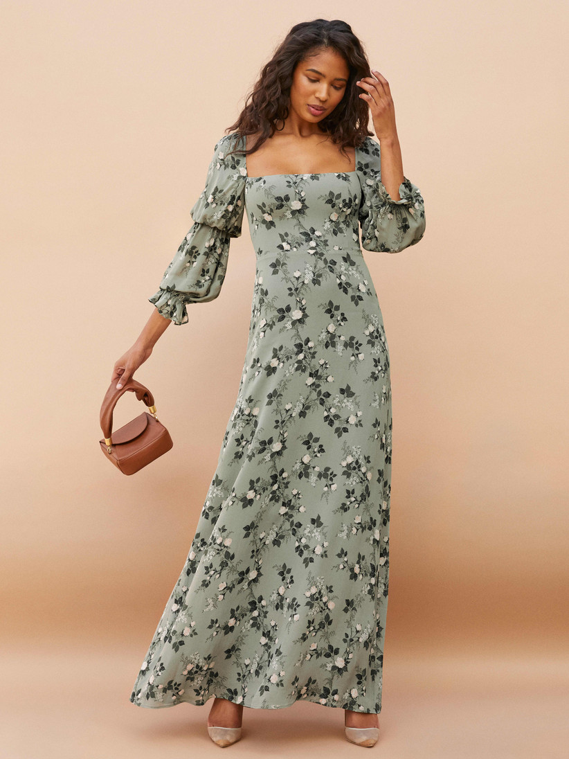 Model wearing sage green maxi with double puffed sleeves and floral print in varying shades of green
