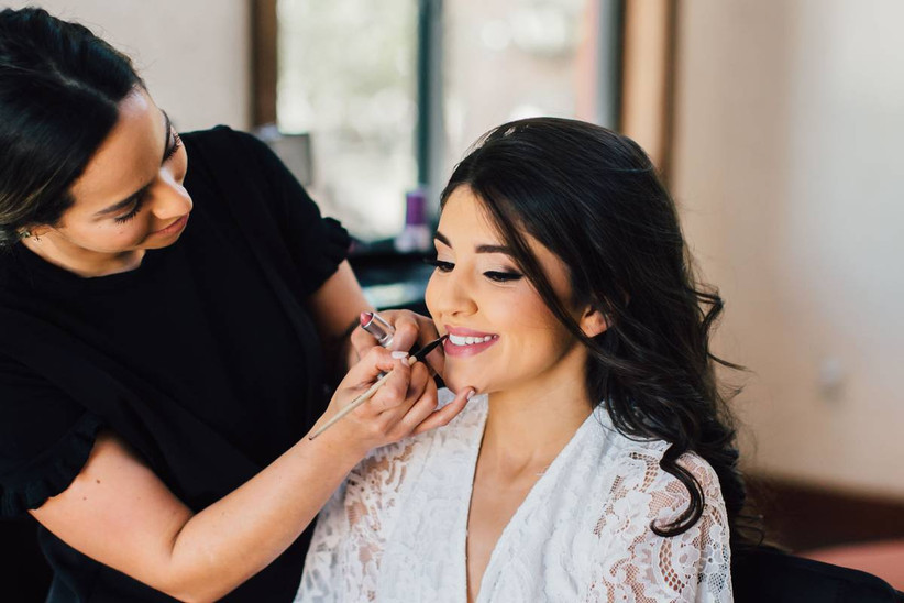 bride wearing white lace robe gets her lipstick applied by professional makeup artist