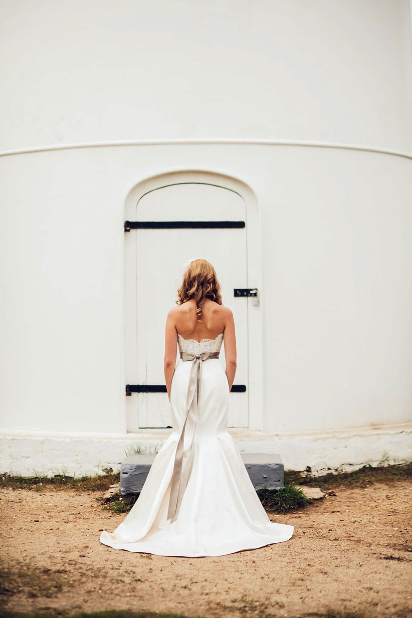 Bride wearing fitted trumpet silhouette wedding dress facing away from the camera