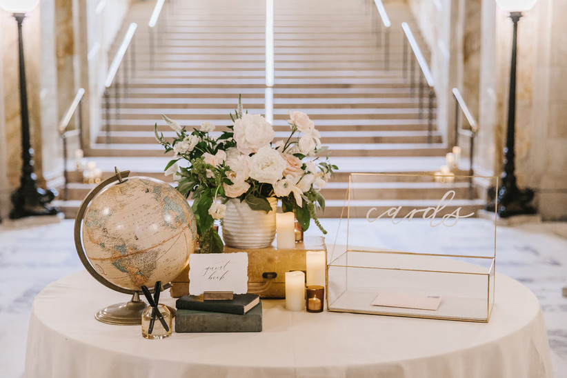 Welcome table displayed at the base of a staircase with glass card box, globe wedding guest book, and small flower centerpiece