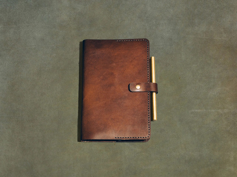 Premium brown leather journal cover with button closure and a pen