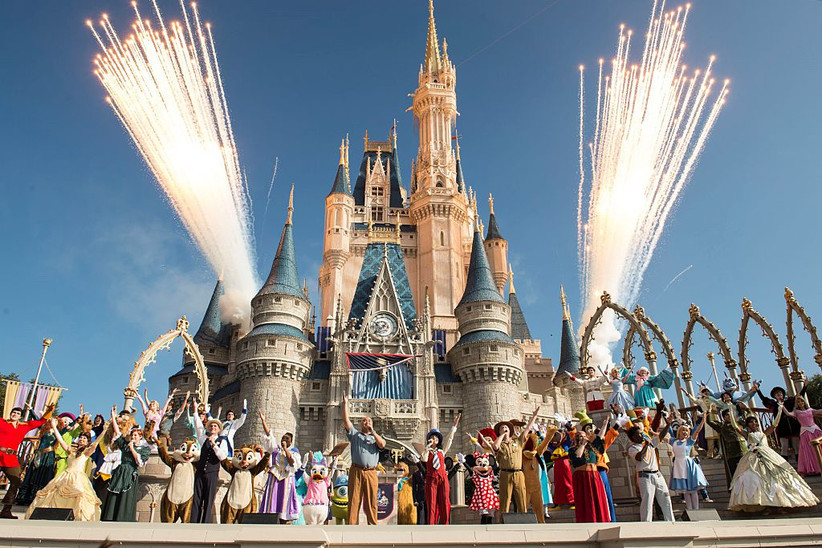 disney characters in front of cinderella's castle at walt disney world with fireworks in background