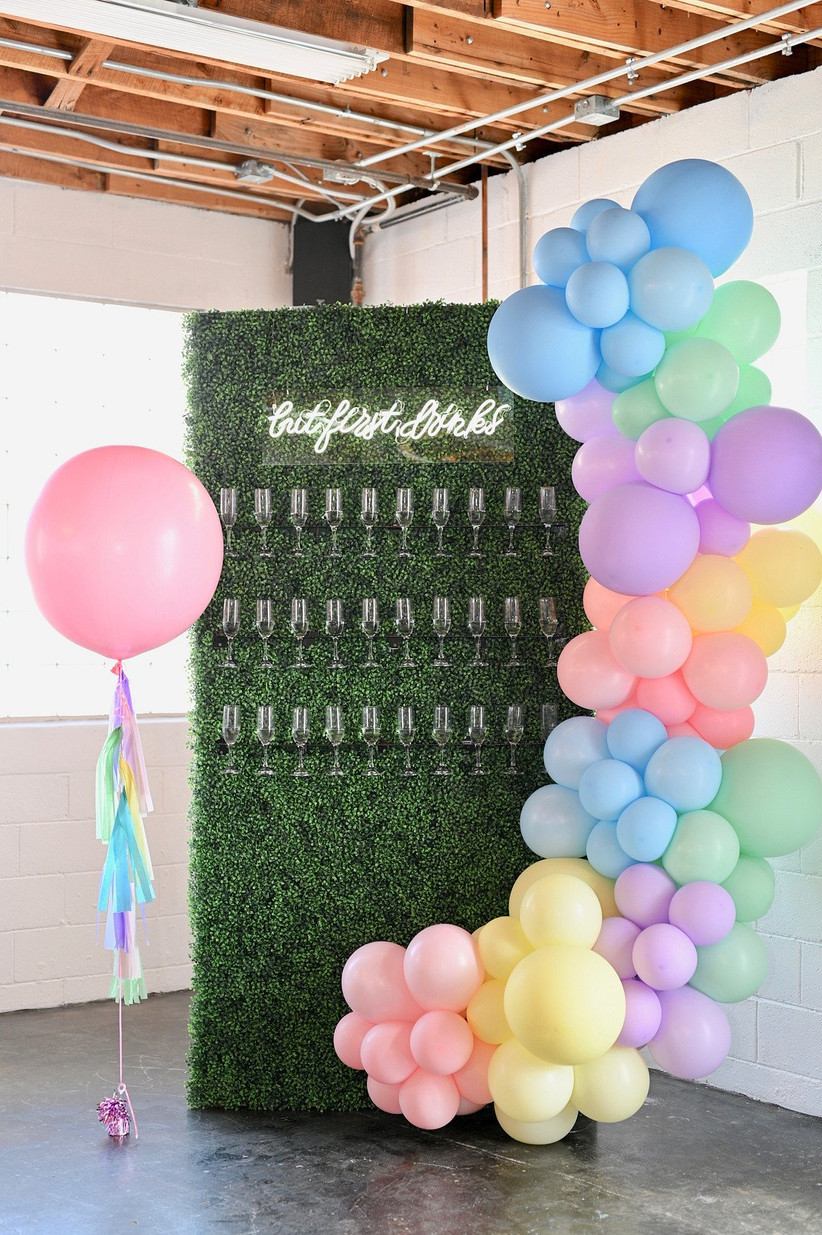 champagne wedding escort card with rainbow balloon arch and