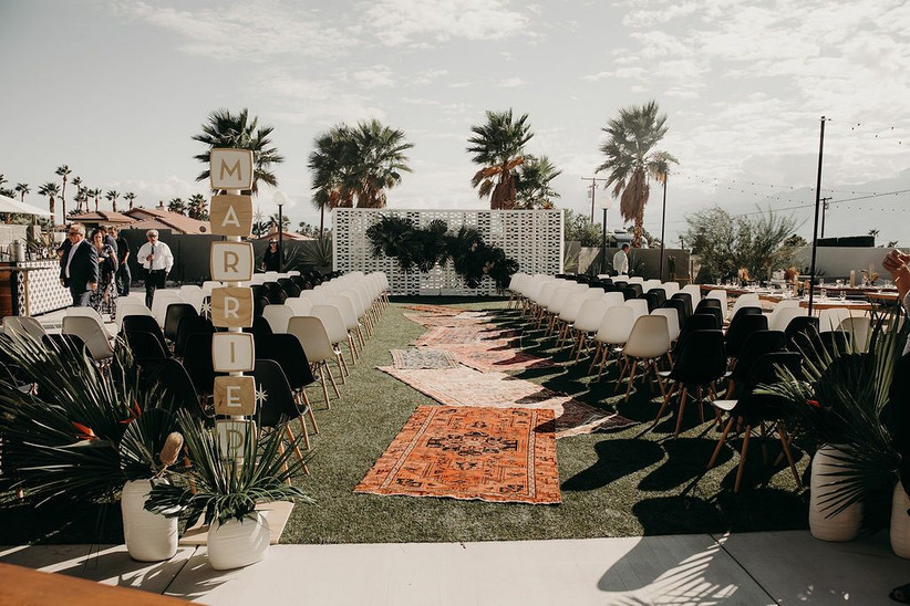 outdoor boho ceremony setting with vintage rugs lining the aisle