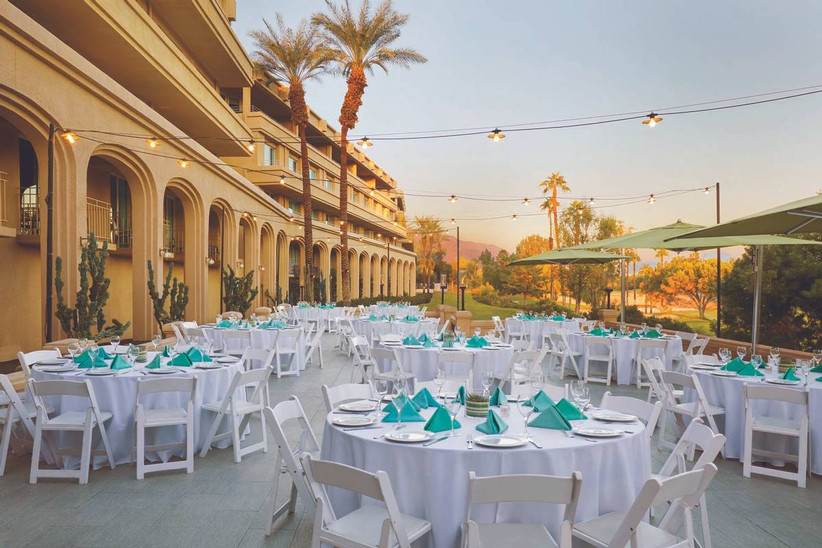 outdoor wedding reception with white tables and turquoise napkins