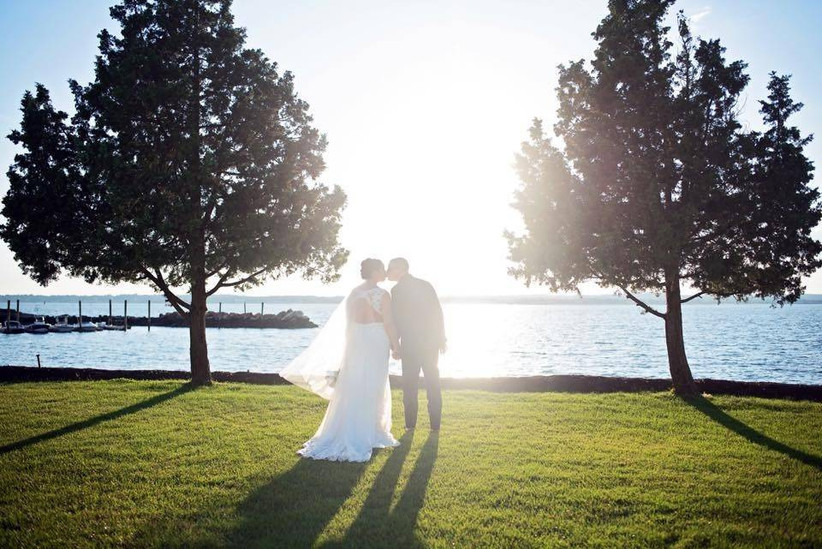 bride and groom kissing near the water