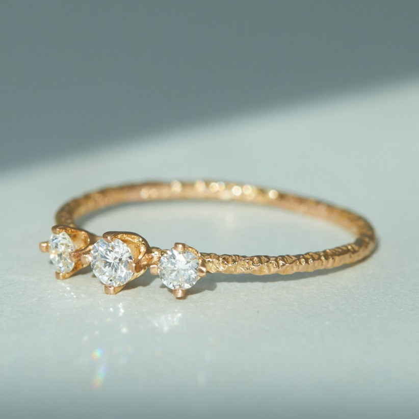 Dainty three-stone engagement ring with textured yellow gold band