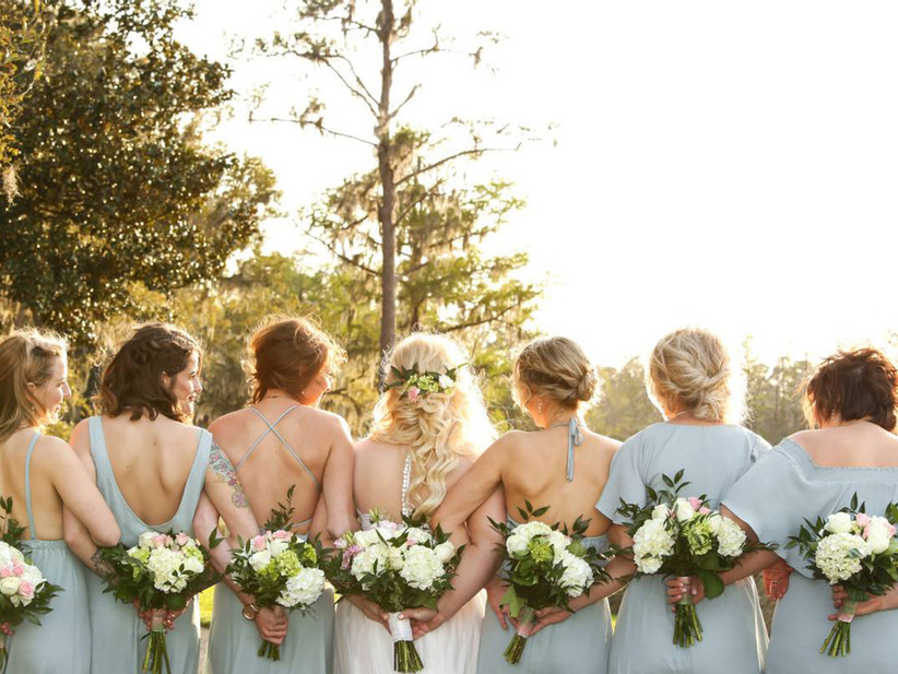 bridesmaids holding bouquets behind their backs