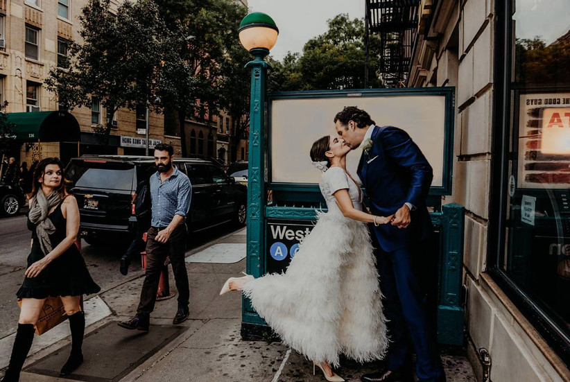 bride and groom kissing outside of nyc subway station