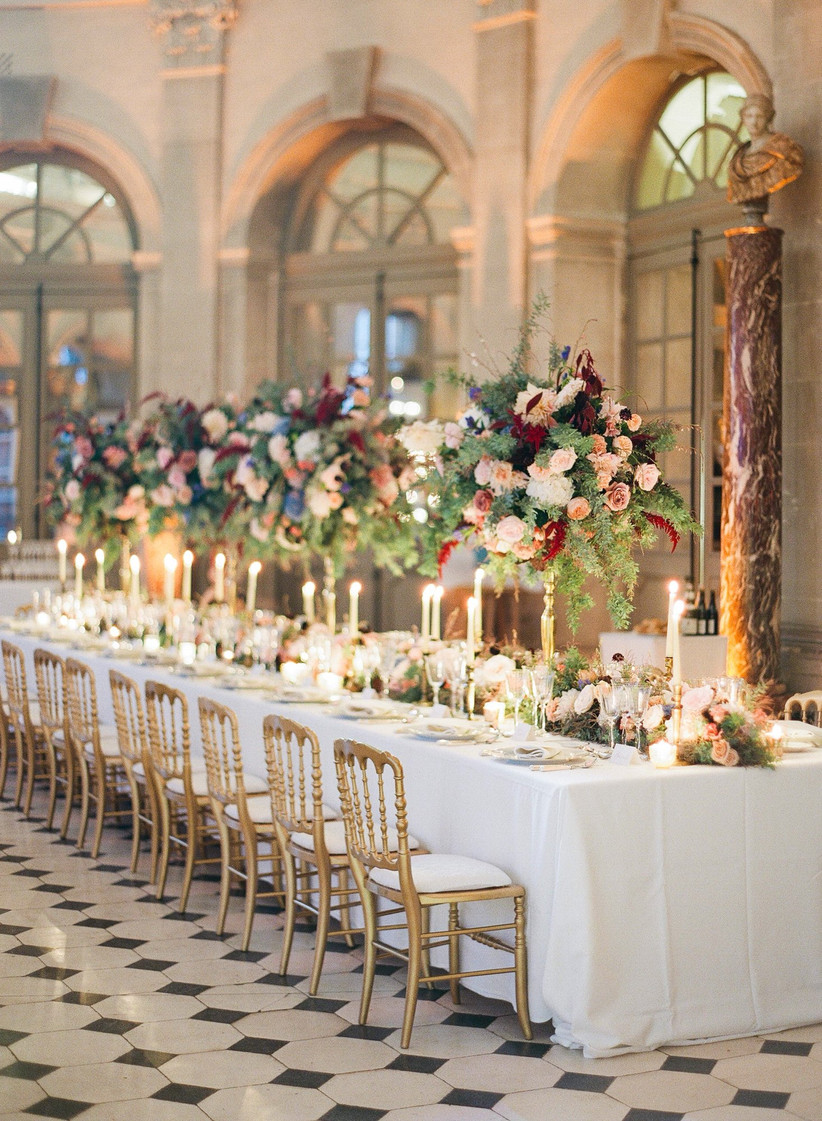 long wedding reception table with tall centerpieces and gold chairs in an elegant historic ballroom