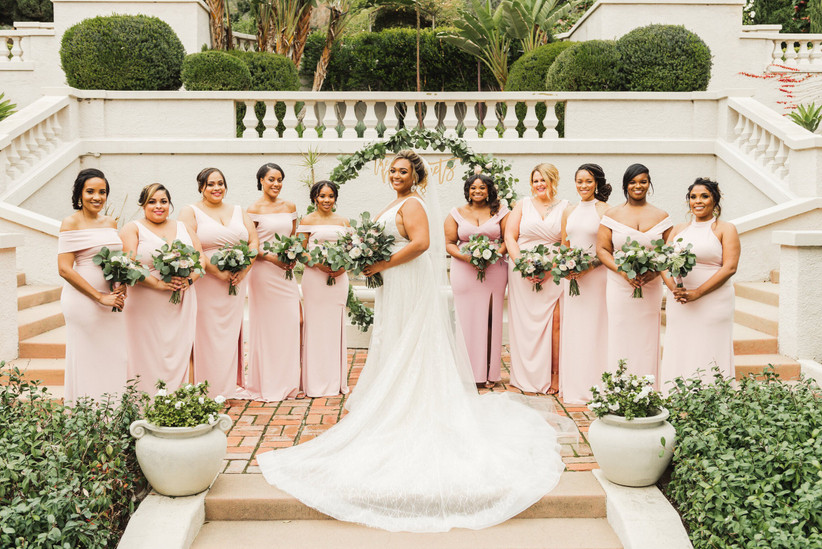 Black bride posing on outdoor staircase with bridesmaids standing behind her holding greenery bouquets