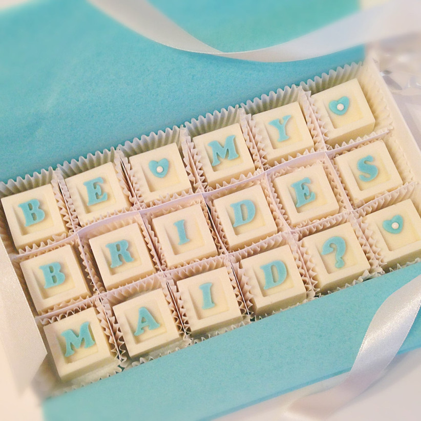 Selection of 18 white chocolates that read Be My Bridesmaid in blue letters