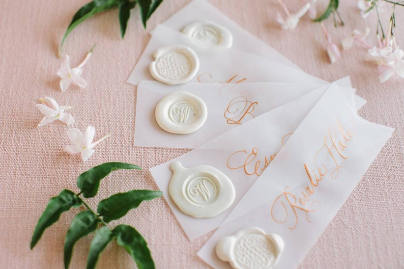 vellum wedding escort cards with rose gold calligraphy and white wax seals