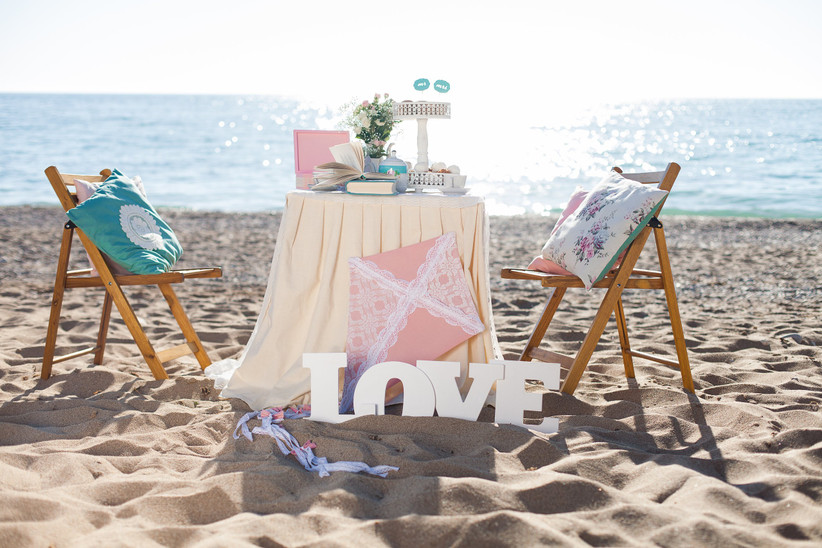 Beach proposal decorations with Love sign, dinner table, and cushions