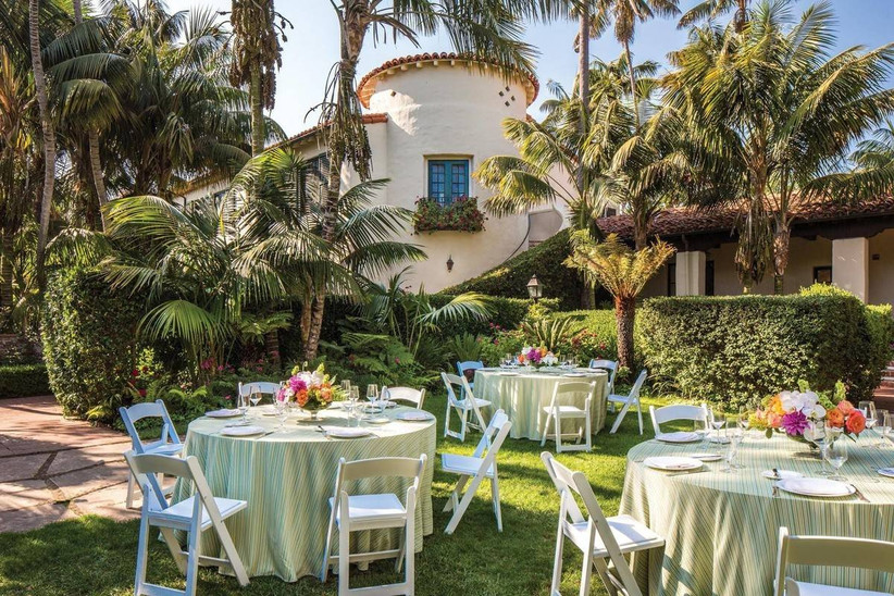 tropical-style garden with palm trees at santa barbara wedding venue. round reception tables are decorated with colorful pink and orange centerpieces