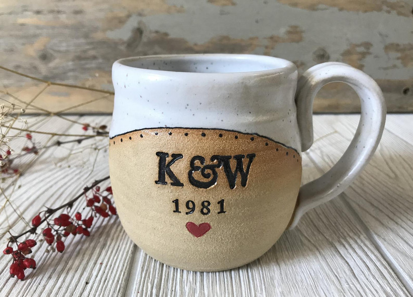 Handmade white and beige pottery mug with coupe's initials in black, the year 1981, and a red heart
