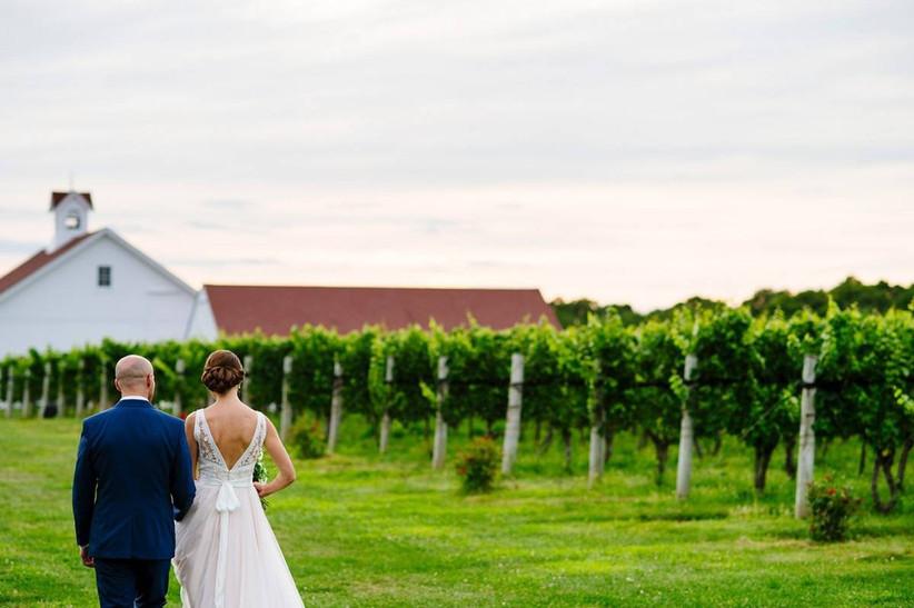 bride and groom walking through vineyards