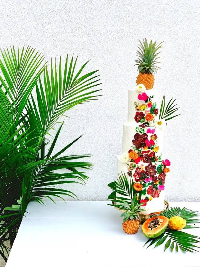 three-tier beach wedding cake decorated with bright icing flowers and palm leaves