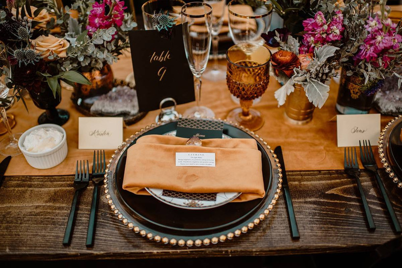 halloween themed wedding idea black and orange place setting with bare wooden table and black flatware