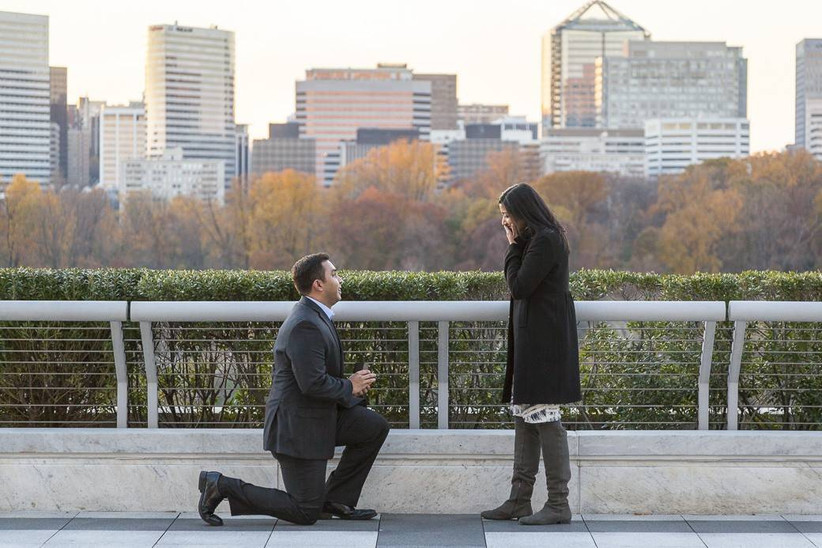 proposal picture of man down on one knee at sunset with bride surprised and city view in the background