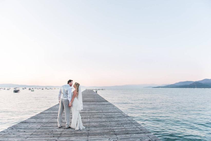 bride and groom walking along a long wooden dock on lake tahoe