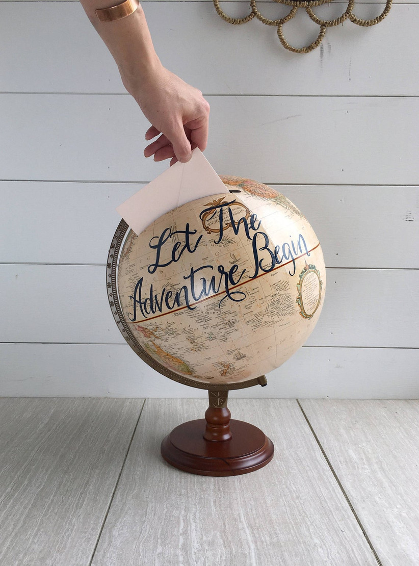 wedding card box made from antique-style globe decorated with let the adventure begin written in calligraphy