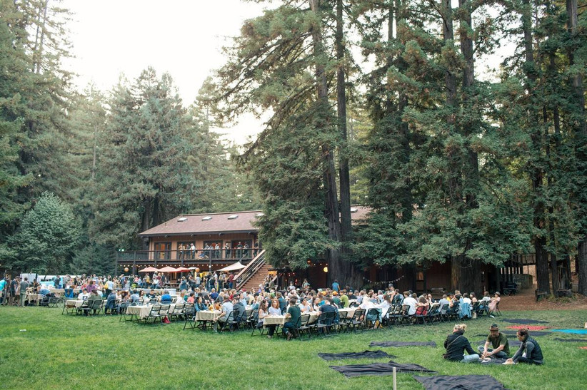 outdoor wedding reception with wooden lodge in background