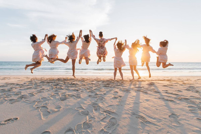 women holding hands and jumping on the beach