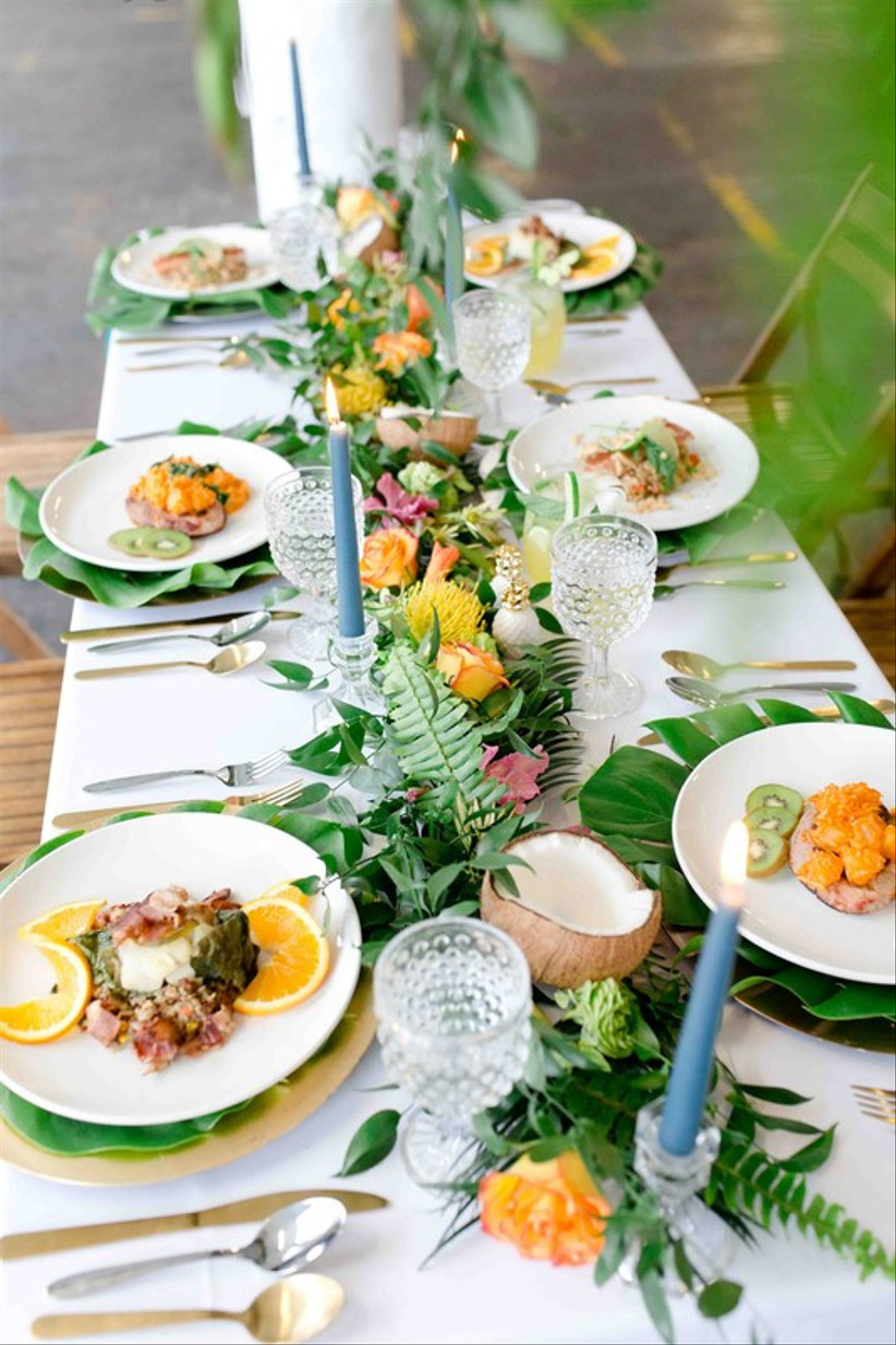 beach wedding centerpiece with ferns, monstera leaves, yellow and pink flowers, and sliced coconuts