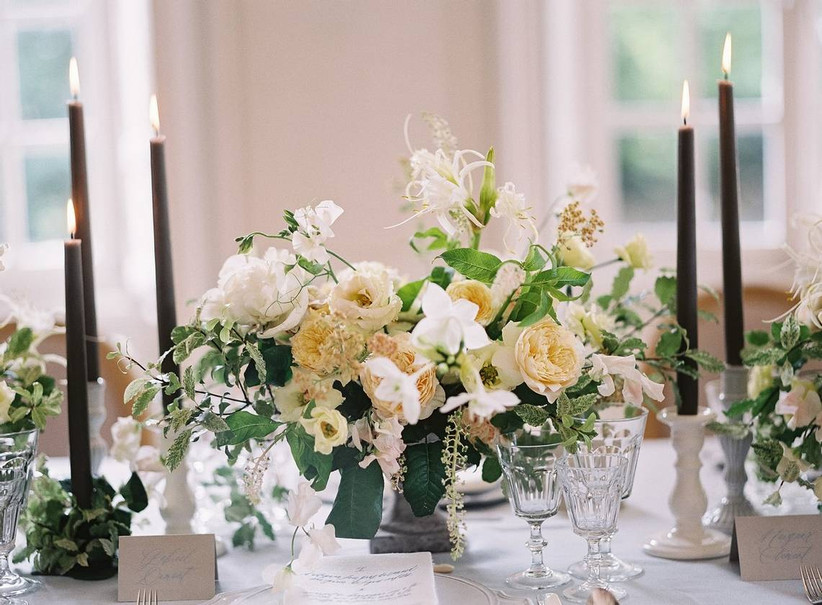pale yellow, white and green low centerpiece with black taper candles on both sides