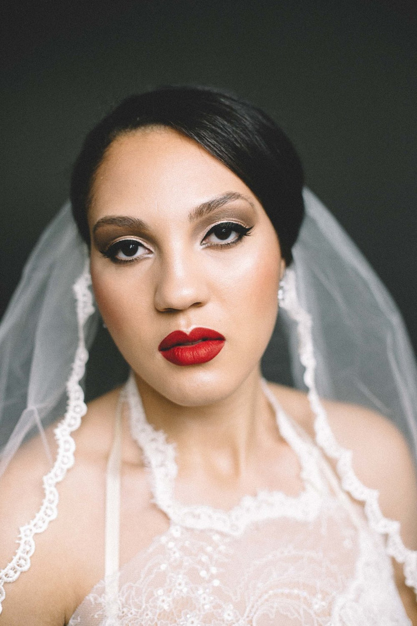 Black bride with glamorous wedding makeup smokey eye with winged liner and red lipstick