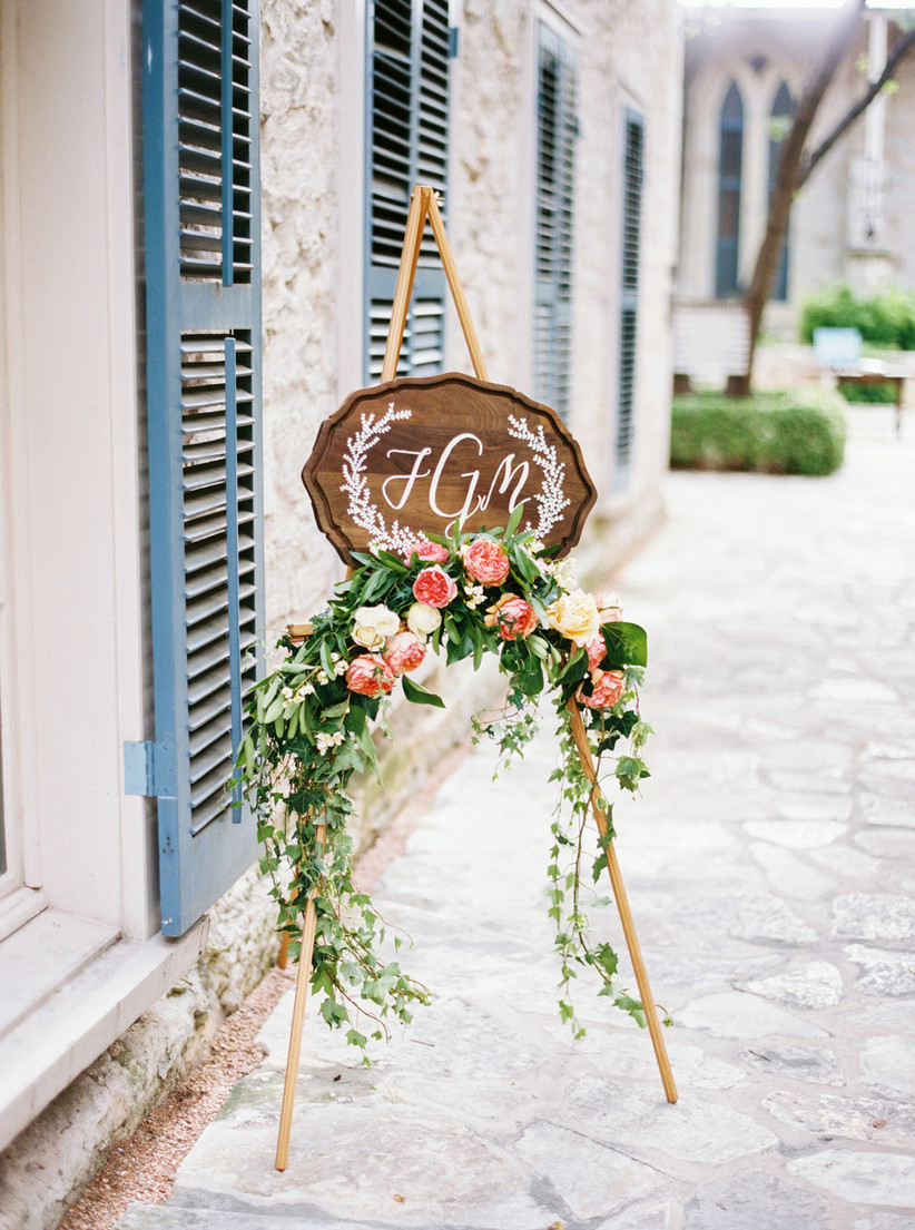 wooden sign featuring couple's monogram in white calligraphy is decorated with pink garden roses and eucalyptus
