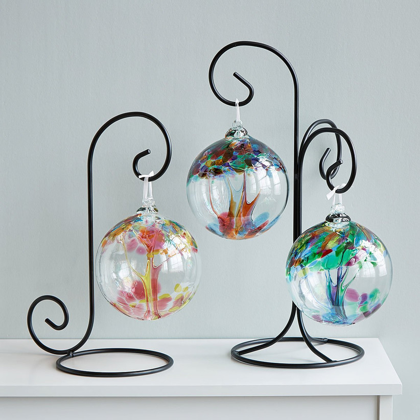 Three colorful glass ornaments hanging from curved black stands