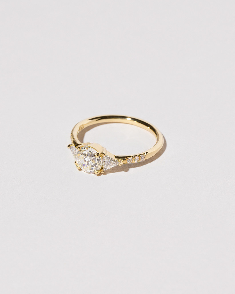 close-up of three-stone engagement ring trend with round center stone and triangle side stones in yellow gold setting