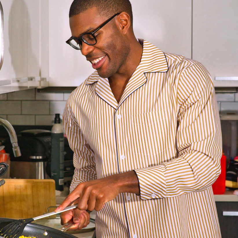 Man wearing comfy striped pajamas from Tie Bar while cooking