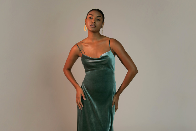 Black model stands with her hands on her hips wearing 2021 bridesmaid dress trend green velvet dress with spaghetti straps and cowl neckline